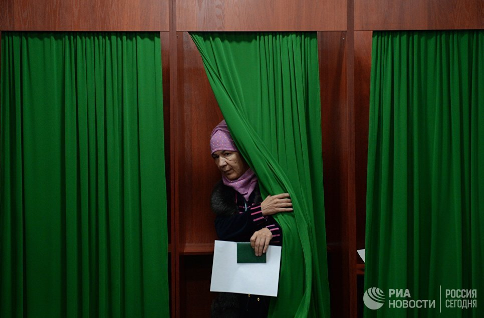 Женщина голосует на избирательном участке во время выборов президента Узбекистана