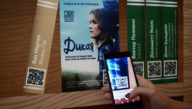 Девушка сканирует QR-код на презентации проекта Мобильные библиотеки в Москве. Архивное фото