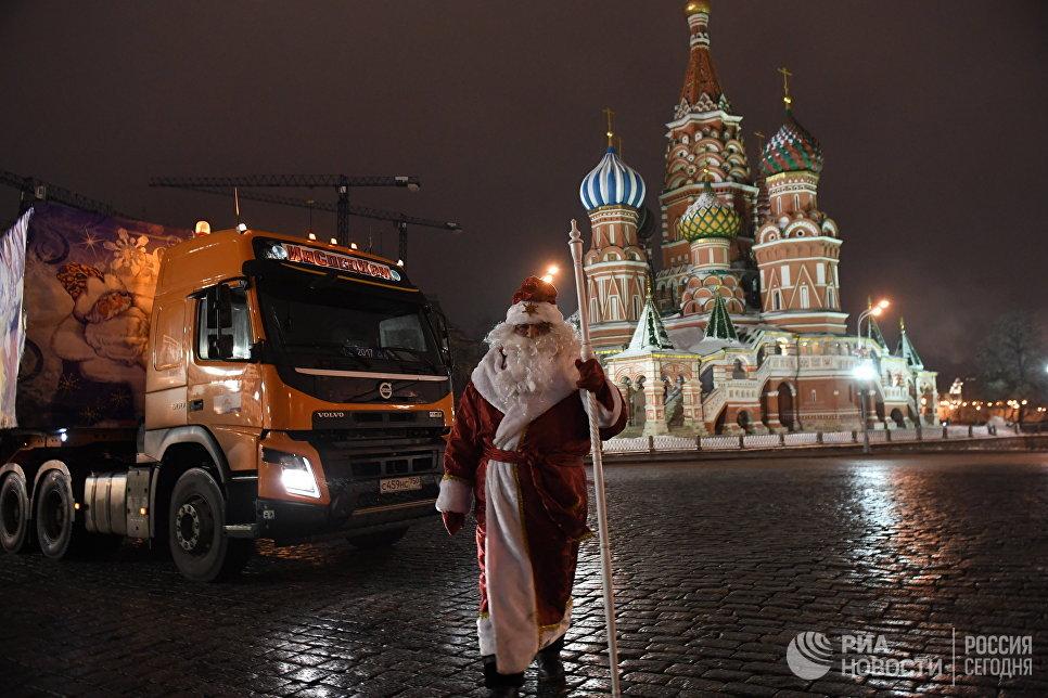 Дед Мороз возле специального автопоезда с главной Новогодней елкой России перед въездом на территорию московского Кремля