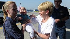 Глава фонда Справедливая помощь Елизавета Глинка помогает женщине с ребенком во время посадки на спецборт МЧС РФ. Архивное фото