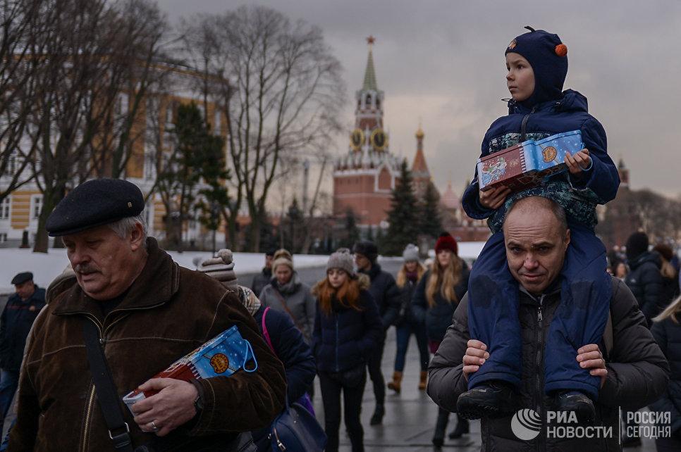 Родители с детьми окончания новогоднего представления в Государственном Кремлевском дворце в Москве