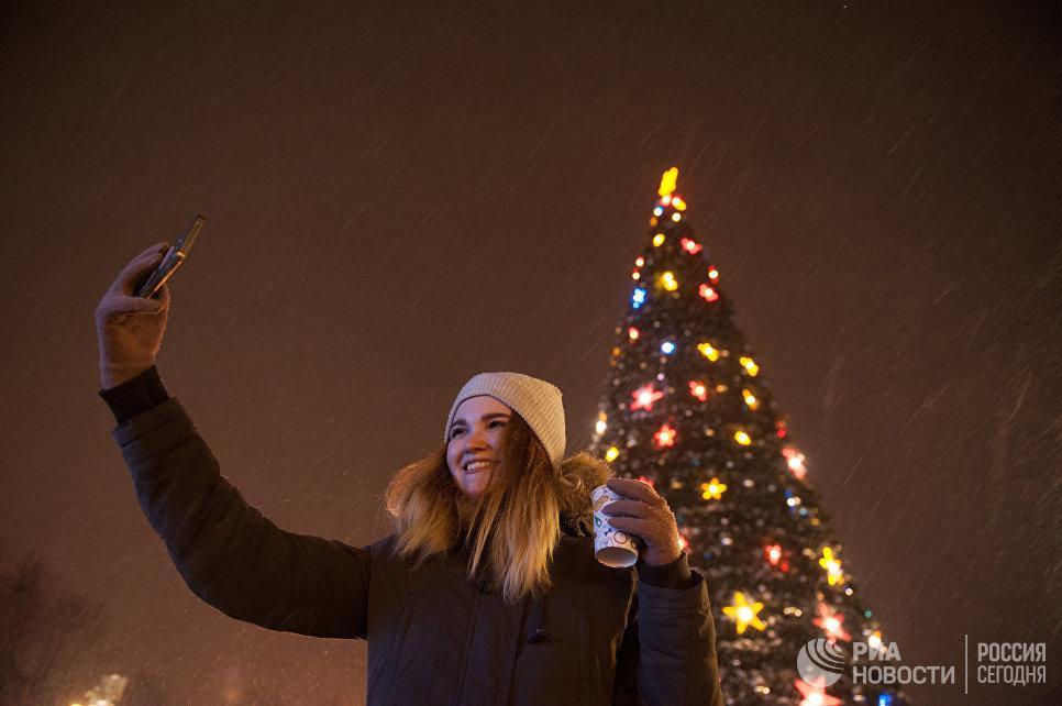 Девушка фотографируется на центральной площади в Томске во время встречи Нового 2017 года