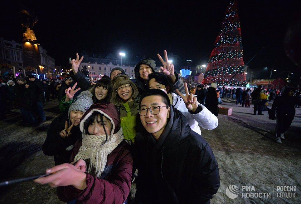 Туристы во время встречи Нового 2017 года на центральной площади во Владивостоке