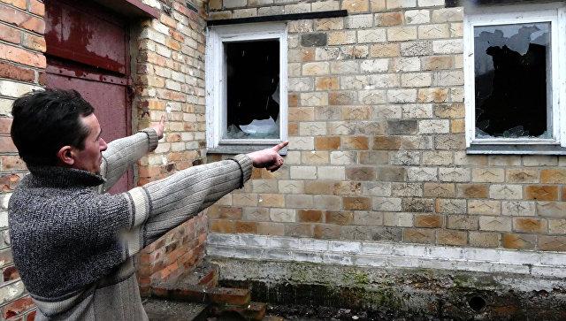 Местный житель показывает разрушения своего дома в поселке Зайцево под Горловкой