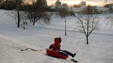 Ребенок катается с горы на берегу Большого Новодевичьего пруда в Москве. Архивное фото