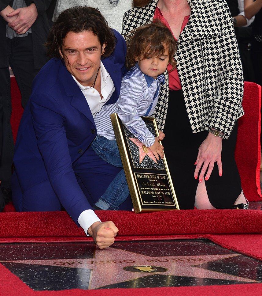 Актер Орландо Блум со своим сыном Флинном на церемонии открытия звезды на Голливудской Аллее Славы, штат Калифорния