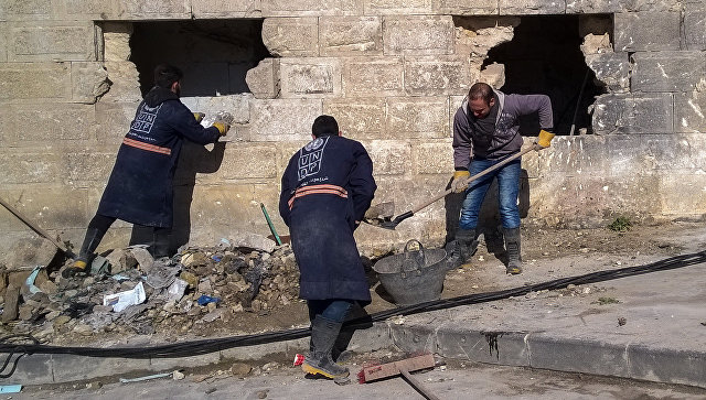 Горожане во время уборке на улице в районе Аль Назирия в сирийском Аллепо. Архивное фото