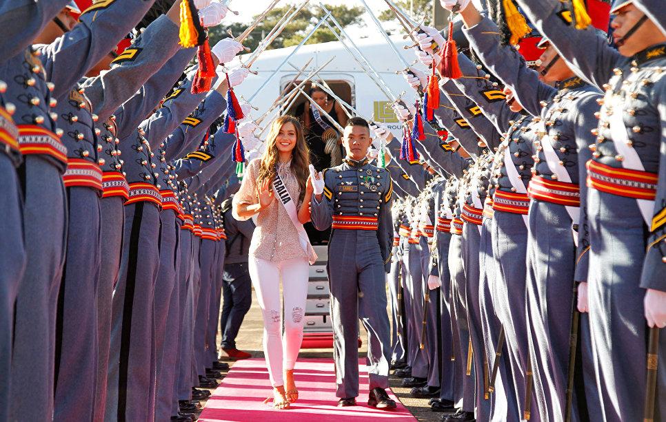 Участница конкурса Мисс Вселенная из Австралии Кэрис Тивель и курсант Филиппинской Военной Академии в аэропорту Багио, Филиппины