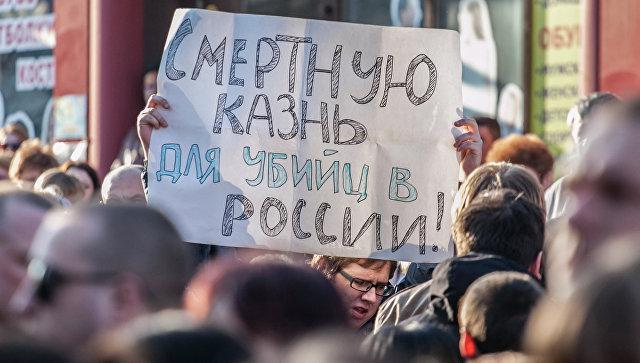 Мужчина держит плакат с требованием смертной казни для виновных в убийствах. Архивное фото