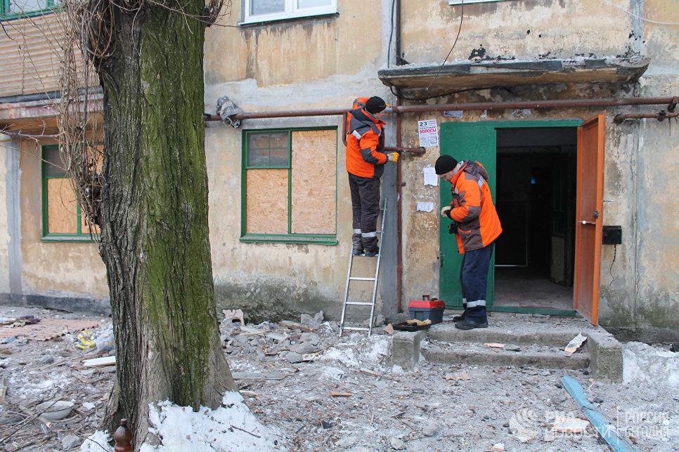 Сотрудники коммунальных служб проводят работы у дома, пострадавшего в результате обстрела украинскими силовиками, в Донецке. 1 февраля 2017
