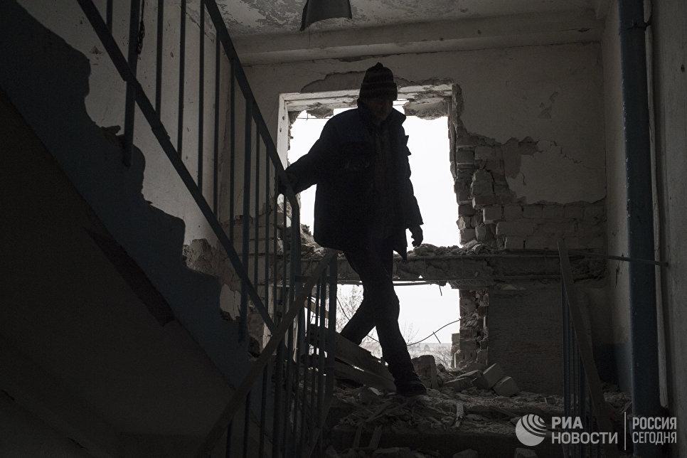 Местный житель в поврежденном в результате обстрелов здании в Киевском районе Донецка
