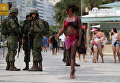 Бразильские военные смотрят на девушку на пляже Копакабана в Рио-де-Жанейро
