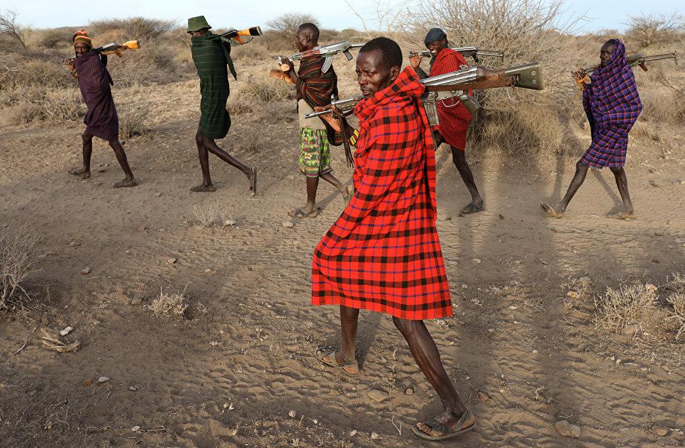 Мужчины из племени Туркана с оружием в руках охраняют скот