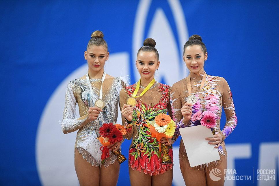 Александра Солдатова (Россия) - второе место, Дина Аверина (Россия) - первое место и Екатерина Галкина (Белоруссия) - третье место в упражнении с обручем в финале индивидуальной программы по художественной гимнастики Гран-при Москвы
