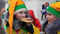 Участники кушают блины во время массового масленичного гуляния Блинно-сырное веселье в Белгороде