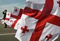Грузинский военный на фоне флагов