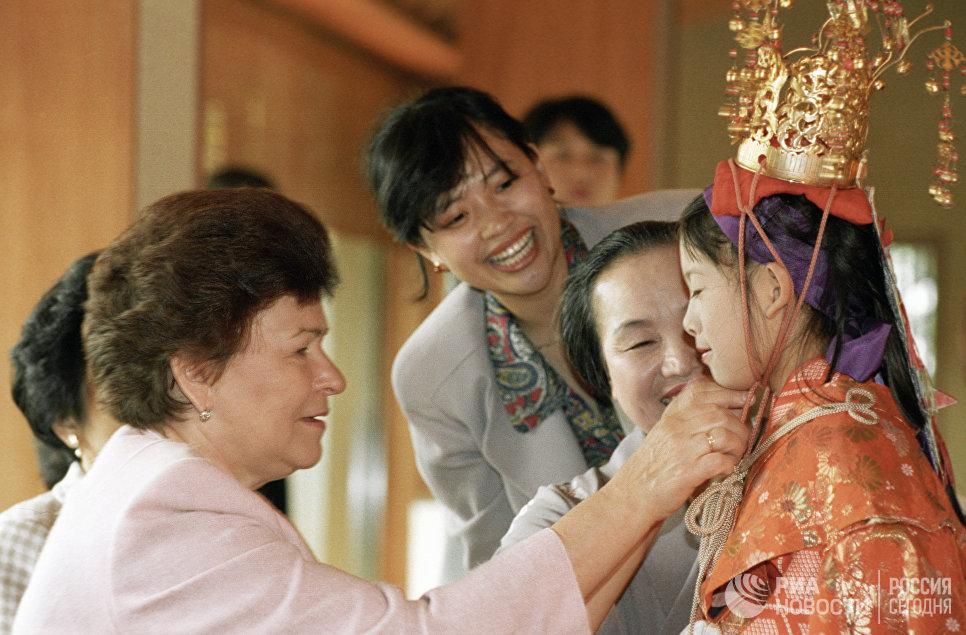 Супруга Президента РФ Наина Ельцина рассматривает наряд юной жительницы Токио на демонстрации коллекции кимоно и искусства икебаны во время визита в Японию