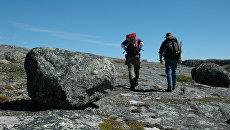 Ученые прогуливаются по скалам, сложенным из первичной коры Земли
