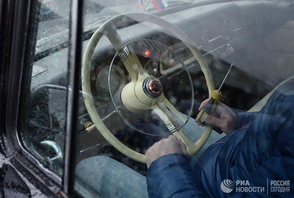 Мужчина в салоне автомобиля ГАЗ 13 Чайка перед стартом автопробега 108 минут в Москве, приуроченного к 56-й годовщине полета человека в космос