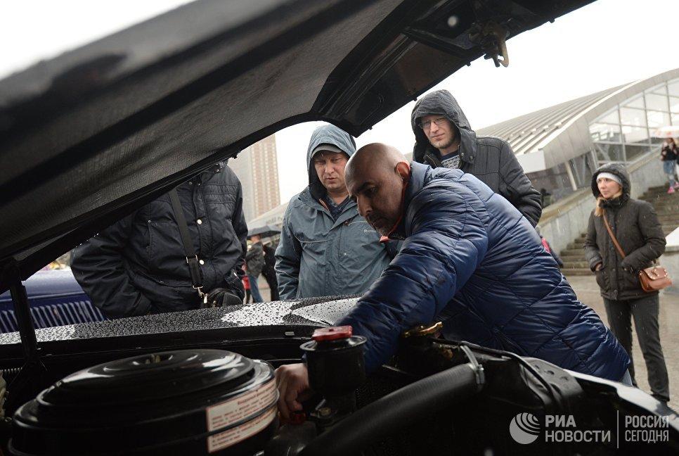 Мужчина ремонтирует ретро-автомобиль перед стартом автопробега 108 минут в Москве, приуроченного к 56-й годовщине полета человека в космос