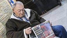 Мужчина читает газету в Хайфе, Израиль