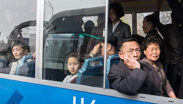 Люди едут в автобусе под одной из улиц в Пхеньяне