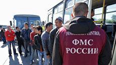 Сотрудник ФМС России с задержанными мигрантами. Архивное фото