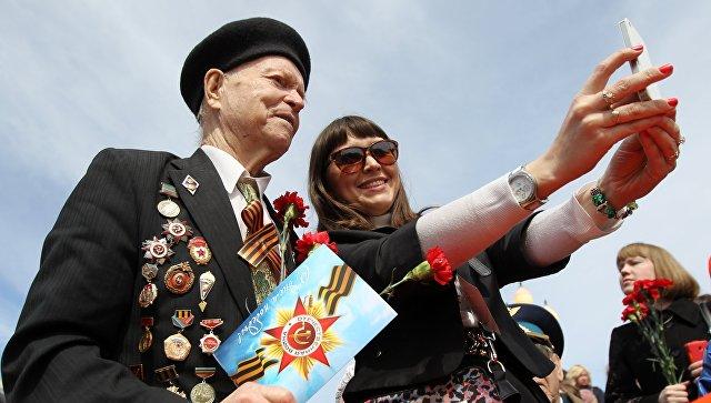 Девушка делает селфи с ветераном во время празднования 70-летия Победы в Великой Отечественной войне. Архивное фото