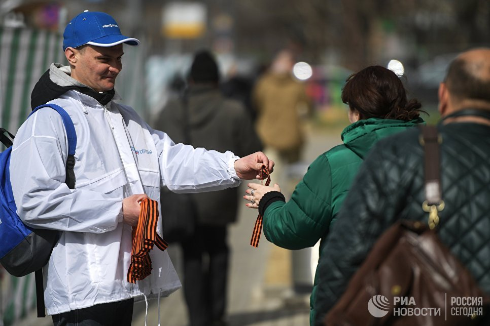 Волонтер раздает георгиевские ленточки на Зубовском бульваре в Москве в рамках стартовавшей ежегодной акции Георгиевская ленточка