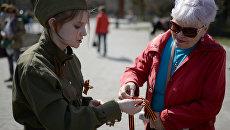 Волонтер Российских студенческих отрядов раздает георгиевские ленточки в Первомайском сквере Новосибирска в рамках ежегодной акции Георгиевская ленточка