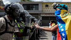 Сотрудники полиции и представители оппозиции во время первомайской демонстрации в Каракасе, Венесуэла