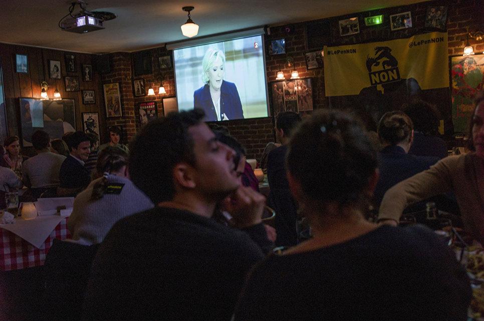 Ресторан транслирует телевизионные дебаты кандидатов в президенты Франции Эммануэля Макрона и Марин Ле Пен. 3 мая 2017