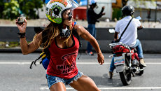 Участница марша против президента Венесуэлы Николаса Мадуро во время столкновений с полицией в Каракасе. Архивное фото