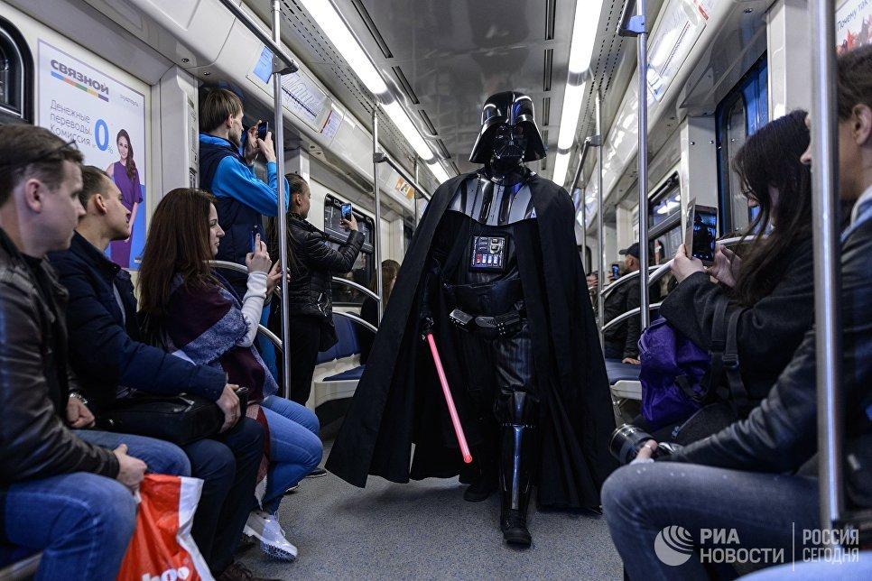 Пассажиры Московского метрополитена фотографируют персонажа фантастического фильма Звездные войны Дарта Вейдера в день Звездных войн