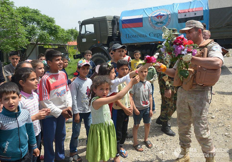 Жители сирийской деревни Брабишбо встречают цветами и апельсинами российских военных, доставивших гуманитарную помощь