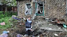Подросток демонстрирует повреждения жилого дома, полученные в результате обстрела Куйбышевского района Донецка. Архивное фото
