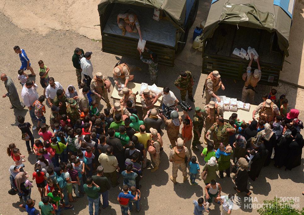 Раздача российской гуманитарной помощи офицерами Центра по примирению враждующих сторон в лагере беженцев Рас-аль-Басит в сирийской провинции Латакия. 3 мая 2017