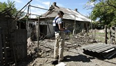 Сотрудник ОБСЕ осматривает двор жилого дома, пострадавший в результате обстрела Докучаевска в Донецкой области. Архивное фото