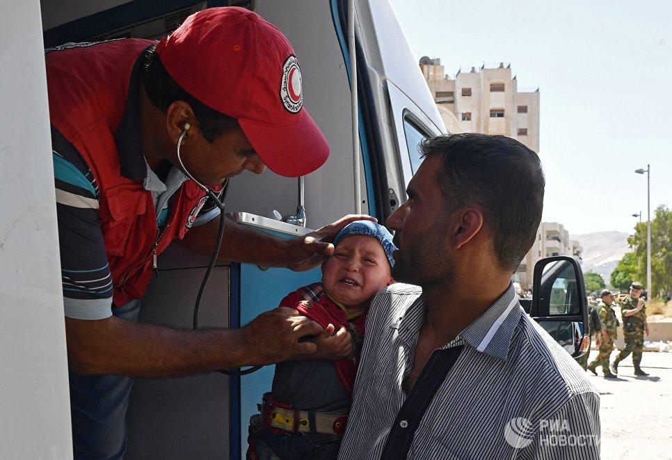 Представители Сирийского арабского красного полумесяца оказывают медицинскую помощь жителям квартала Кабун в пригороде Дамаска