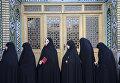 Женщины стоят возле избирательного участка в городе Кум, Иран