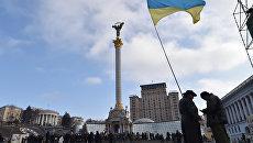 Активисты размахивают украинским флагом на Майдане Незалежности в Киеве