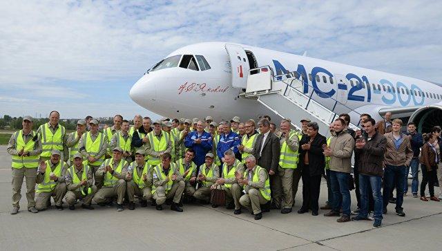 Сотрудники Иркутского авиационного завода у нового российского пассажирского самолета МС-21 после его первого полета
