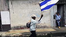 Мужчина размахивает национальным флагом во время протеста, требуя честных выборов в городе Дириамба, примерно в 40 километрах от Манагуа. 16 октября 2016 года