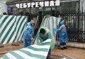 Строители поднимают сорванный ураганом заградительный забор на улице Остоженка в Москве