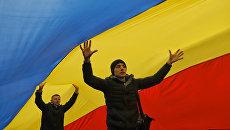 Люди ходят под флагом Молдавии во время акции протеста в Кишиневе 14 ноября 2016