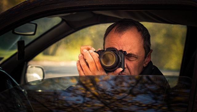 Мужчина фотографирует из окна автомобиля