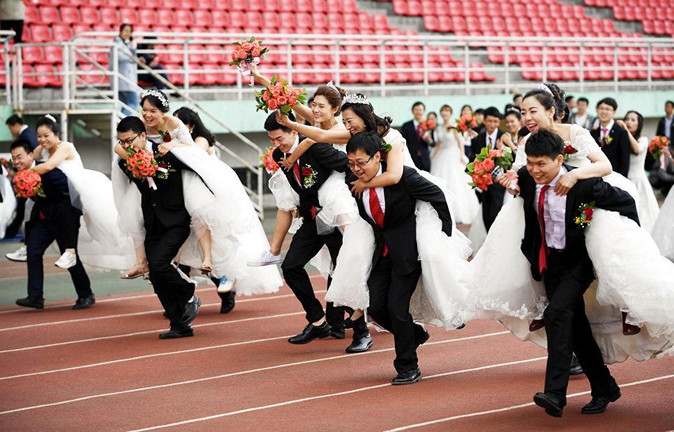 Пары принимают участие в конкурсе во время массовой свадьбы в Китае