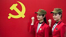 Девушки фотографируются с флагом Коммунистической партии Китая в Шаошане. Архивное фото