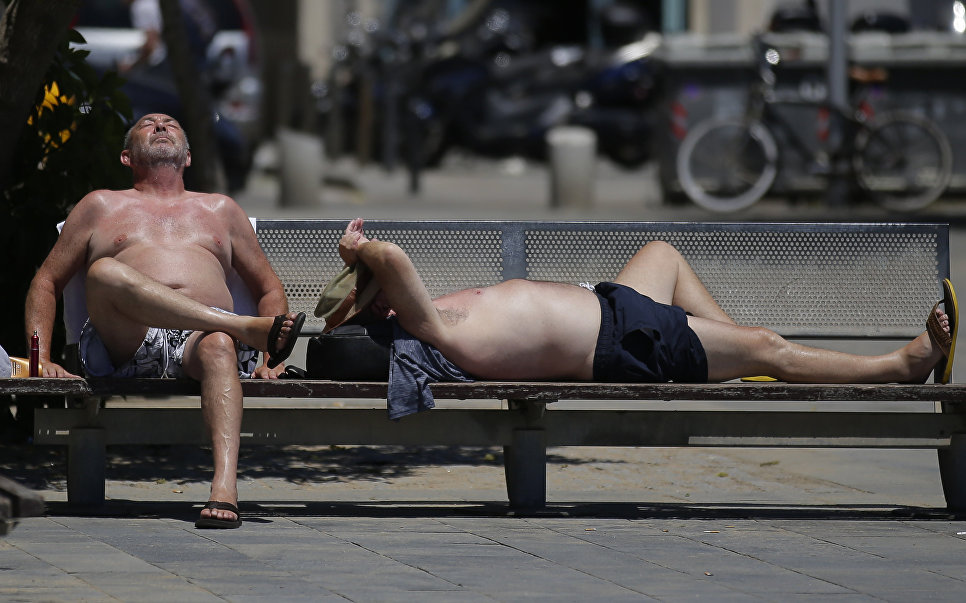 Мужчины загорают на пляже Барселонеты, Испания