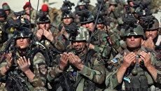 Служащие сил безопасности Афганистана совершают молитву во время церемонии  происходящей к востоку от Кабула, после того как НАТО завершила свою 13-летнюю миссию в Афганистане
